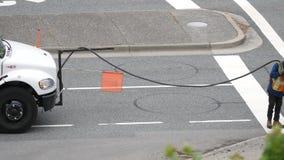 Motie van arbeider het vullen asfalt op weg na groot regenend seizoen stock footage