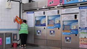 Motie van arbeiders schoonmakende vloer en muur dichtbij kaartjesmachine stock footage