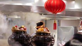 Motie van chef-kok die voedsel voor klant voorbereiden bij delicatessenwinkelgebied binnen Chinees restaurant stock footage