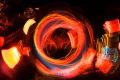 Motie van de hoge resolutie vertroebelde de Abstracte gloeiende cirkel achtergrond in donkere levendige rood, groen, geel, blauw Stock Foto