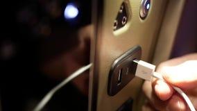 Motie van de mens die USB-kabel voor het laden van zijn slimme telefoon opnemen