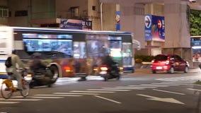 Motie van forenzen en auto's die door weg bij nacht overgaan stock video