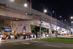 Motie van forenzen en auto's die door weg bij nacht overgaan stock foto