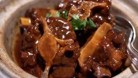 Motie van gestoofde ossestaart en radijs binnen kleine pot bij Chinees restaurant stock video