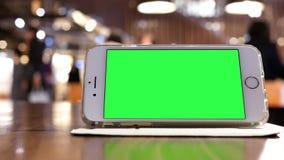 Motie van groene het schermtelefoon met en onduidelijk beeldmensen die winkelen rusten stock video