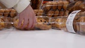 Motie van mensen die de werveling van de rozijnenbrioche binnen Costco-opslag kopen stock footage