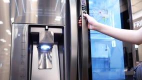 Motie van mensen die een nieuwe koelkast binnen elektronische opslag proberen stock video