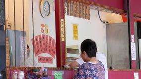 Motie van mensen die gestoomd broodje kopen bij kleine winkel stock footage