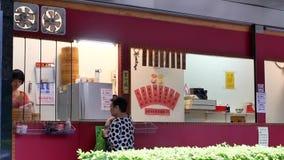 Motie van mensen die gestoomd broodje kopen bij kleine winkel bij regenende nacht stock video