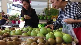 Motie van mensen die guave binnen opslag van het prijs de slimme voedsel kopen stock video