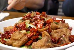Motie van mensen die hete kruidige gebraden kip op lijst eten Stock Afbeelding