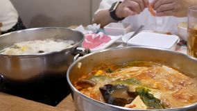 Motie van mensen die hete pot eten die binnen Chinees restaurant koken stock video