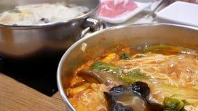 Motie van mensen die hete pot eten die binnen Chinees restaurant koken stock footage