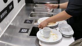 Motie van mensen die resterend voedsel schoonmaken bij de sorterende post van het voedselhof stock videobeelden