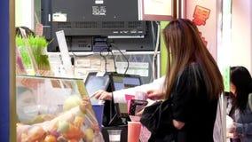 Motie van mensen die sap kopen en contant geld betalen stock footage