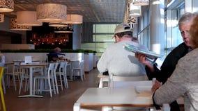 Motie van mensen die van maaltijd genieten bij de cafetaria van het voedselhof stock videobeelden