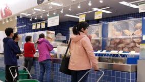 Motie van mensen die vissen kopen bij zeevruchtensectie stock videobeelden