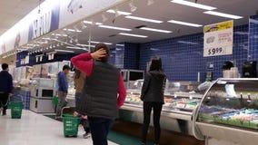 Motie van mensen die vissen kopen bij zeevruchtensectie stock video
