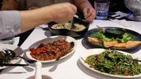 Motie van mensen die voedsel met familie binnen het restaurant van Thailand eten stock footage