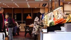 Motie van mensen die voedsel nemen bij delicatessenwinkelgebied binnen Chinees restaurant stock video
