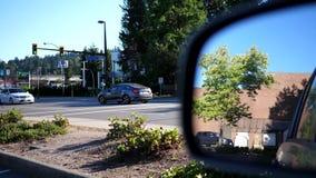 Motie van verkeersstroom op straat en achterspiegelauto die voor parkeren overgaan stock footage
