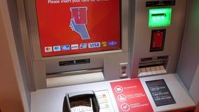 Motie van vrouw die bandkaart opnemen en geld terugtrekken bij ATM-machine stock video