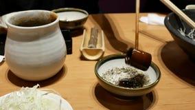 Motie van vrouwen gietende saus op sesam bij Japans restaurant stock videobeelden