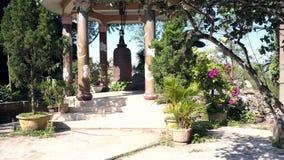 Motie voorbij bloemen om paviljoen met reusachtige klok te marmeren stock footage