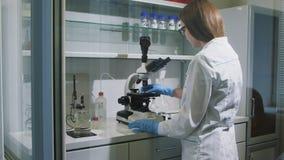 Motie voorbij de medewerker die van het meisjeslaboratorium microscoop tijdens test bekijken stock video