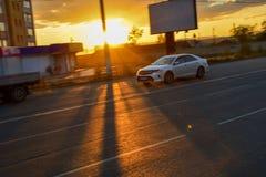 Motieauto op de weg in de stad op een achtergrond van de zon` s stralen door De zonsondergang met mooie zonstralen in stad Stock Foto's