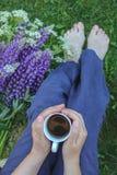 Motief van een blootvoetse vrouwenzitting in een tuin met wilde bloemen en een kop van koffie stock afbeelding