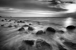 Motiegolven op stenen bij het strand Stock Foto