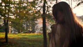 Motielengte, schitterend Kaukasisch meisje in profiel die en dichtbij camera in gouden dalingspark maaien lopen en gelukkig stock videobeelden