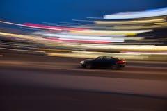 Motieonduidelijk beeld van een auto in een kromme met stads lichte slepen Stock Afbeelding