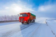 Motieonduidelijk beeld van een rode stortplaatsvrachtwagen met lading op de winterweg stock fotografie