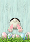 Motif de Pâques, fond de lapin et oeufs de pâques dans l'herbe fraîche sur le fond en bois bleu, illustration