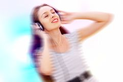 In motion. Blurrier portrait   of young  female listening music via earphones. Focused on face Stock Images