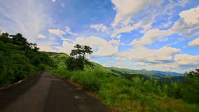 Motion along Curvy Country Road among Green Hilly Landscape. DA LAT, LAM DONG/VIETNAM - SEPTEMBER 02 2016: Camera moves along curvy ground country road among stock video