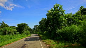Motion along Curvy Road among Green Landscape past Car stock video