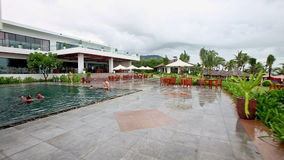 Motion along hotel swimming pool side tourist walks after rain stock video footage