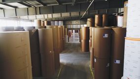 Motion along pass between paper rolls in factory storage. Motion along pass between large packaging paper rolls with stickers in brightly lit factory storage stock video footage
