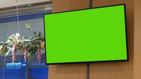 Motion of big green screen tv on wall. Inside shopping mall stock video