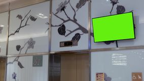 Motion of big green screen tv on wall. Inside shopping mall stock video footage