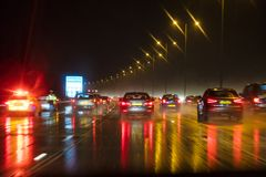 Motion Blur British Motorway Traffic and Police. Motion blurred photograph of traffic at in night in the rain on a British motorway with police officer and car Royalty Free Stock Photography