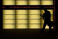 Motion blur of a business man. Motion blur of a man passing an advertisement board stock photos
