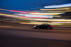 Motion blur of a car in a curve with city light trails Stock Image