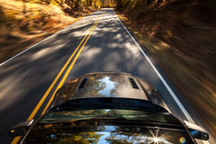 Motion blur of car driving down a road during Fall Stock Images