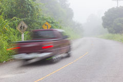 Motion blur of car on road on foggy morning along green tree lin Royalty Free Stock Images