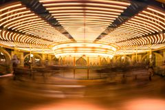 Motion blur carousel or merry-go-round. Motion blur abstract picture of carousel or merry-go-round with light up decoration at night stock photos