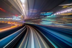 Motion blur of a city and tunnel from inside a moving monorail in Tokyo stock photo